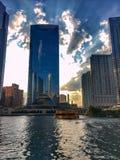 El taxi del agua flota en el río Chicago mientras que las reflexiones de la puesta del sol y de edificios como sistemas del sol fotos de archivo