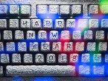 El teclado cubierto con nieve con la Feliz Año Nuevo 2018 del título se encendió por las luces coloridas Imagen de archivo