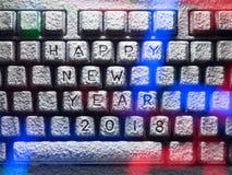 El teclado de ordenador cubierto con nieve con la Feliz Año Nuevo 2018 del título se encendió por las luces coloridas Imagenes de archivo