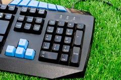El teclado de ordenador negro viejo encendido adorna la hierba artificial verde Fotografía de archivo