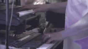 El teclista juega en varios instrumentos musicales en un concierto como parte de un grupo musical almacen de video
