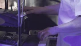 El teclista juega en varios instrumentos musicales en un concierto como parte de un grupo musical almacen de metraje de vídeo