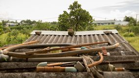 El tejado acanalado sucio del vintage con los tubos de agua abandonados riega las válvulas plásticas y a Rusty Metal Junk - jardí fotos de archivo libres de regalías