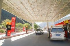 El tejado blanco que la gasolinera de acero se mezcla pone el combustible diesel en los coches gasolina-accionados en Daocheng-Ya imagen de archivo