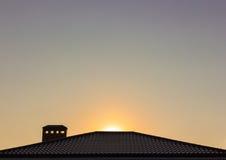 El tejado en el fondo de la puesta del sol Fotografía de archivo libre de regalías