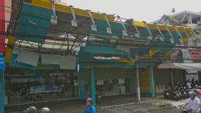 El tejado quebrado del edificio cuelga en los alambres eléctricos después de huracán