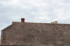 El tejado triangular que se inclina antiguo viejo de la casa, la cabaña es sucio con los colmillos demasiado grandes para su edad imagen de archivo libre de regalías
