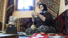 El tejer de la alfombra. Mujer envejecida del turco con el ovillo de seda