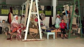 El tejer de la alfombra. Tres alfombra-fabricantes de la mujer. Fábrica que teje en Túnez almacen de video