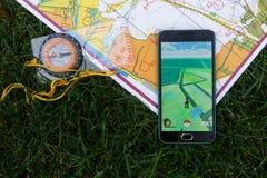 El teléfono con Pokemon va uso en la pantalla, mapas y compas Imagen de archivo libre de regalías
