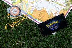 El teléfono con Pokemon va uso en la pantalla, mapas y compas Fotos de archivo