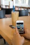 el teléfono elegante del control de la mano de la mujer toma una imagen Fotos de archivo libres de regalías