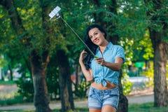 El teléfono elegante del uso del monopod del control de las mujeres toma la fotografía Imagen de archivo libre de regalías