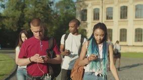 El tel?fono envici? a los estudiantes diversos que caminaban en campus almacen de video