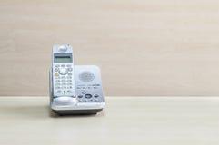 El teléfono gris del primer, el teléfono de la oficina en el escritorio de madera borroso y la pared texturizaron el fondo en la  imágenes de archivo libres de regalías