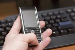 El teléfono móvil adentro sirve la mano Imagen de archivo libre de regalías