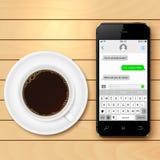 El teléfono móvil con SMS charla en la taza de la pantalla y de café en la tabla de madera Imagen de archivo
