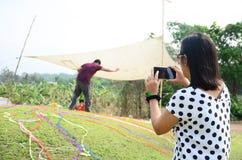 El teléfono móvil del uso tailandés de las mujeres toma ceremonia de la foto Imagenes de archivo