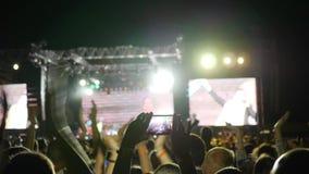 El teléfono móvil a disposición hace la foto de la etapa iluminada en el festival de la roca, gente salta y palmada en el concier almacen de video