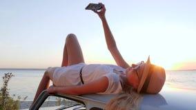 El teléfono móvil en viaje feliz, muchacha linda con el teléfono en las manos miente en el tejado del coche, imágenes que el telé almacen de video
