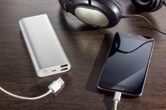 El teléfono móvil y el poder depositan la batería en fondo oscuro imagen de archivo libre de regalías