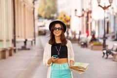 El teléfono móvil y la ciudad de los controles de la mujer trazan como turista Foto de archivo