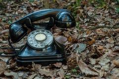 El teléfono negro en la tierra por completo de hojas Imagen de archivo libre de regalías