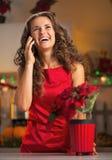 El teléfono que hablaba del ama de casa feliz en la Navidad adornó la cocina Imágenes de archivo libres de regalías