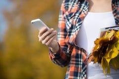 El teléfono que se sostiene femenino disponible, amarillo se va en otro Imágenes de archivo libres de regalías