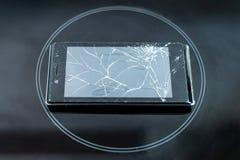 El teléfono quebrado descansa sobre un vidrio esmerilado negro, en el centro del círculo fotos de archivo
