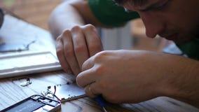 El teléfono roto de reparación principal, mira fijamente, recoge las pequeñas piezas, que están en la tabla, conecta la prensa de almacen de video