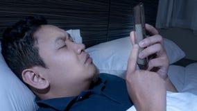 El tel?fono envici?, hombre usando el tel?fono elegante en cama a la medianoche imagen de archivo libre de regalías