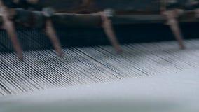 El telar funciona con la tela blanca en una planta de materia textil metrajes