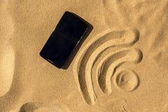 El teléfono móvil en la playa y WiFi firman Fotos de archivo libres de regalías