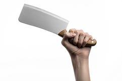 El tema de la cocina: Mano del cocinero que sostiene un cuchillo de cocina grande para cortar la carne en un fondo blanco aislado Imagen de archivo libre de regalías