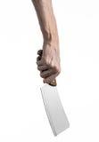 El tema de la cocina: Mano del cocinero que sostiene un cuchillo de cocina grande para cortar la carne en un fondo blanco aislado Imágenes de archivo libres de regalías