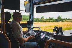 El tema es la profesión del transporte del conductor y del pasajero Un hombre en conductor de las gafas de sol A clava un autobús imagen de archivo