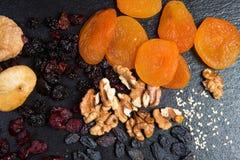 El tema es un postre dulce hecho de productos naturales sin el azúcar Cierre macro encima del sistema de los frutos secos del pos foto de archivo