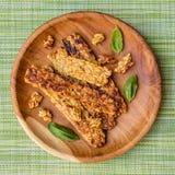 El tempeh frito adornado con albahaca se va en una bandeja de madera redonda sobre servilleta verde Visión superior Imagen cuadra Foto de archivo