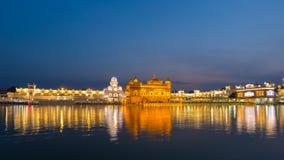 El templo de oro en Amritsar, Punjab, la India, el icono más sagrado y el lugar de la adoración de la religión sikh Iluminado en  Foto de archivo