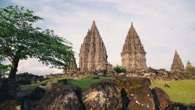 El templo de Prambanan y el césped verde resbalan el día soleado metrajes