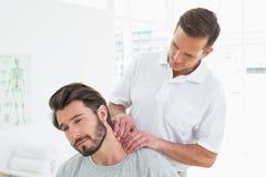 El terapeuta de sexo masculino que da masajes a un joven sirve el cuello fotografía de archivo libre de regalías