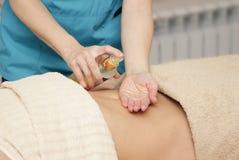 El terapeuta del masaje aplica el aceite para el masaje fotos de archivo