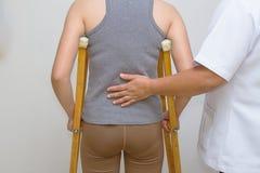 El terapeuta físico ayuda a una rehabilitación paciente para caminar Foto de archivo libre de regalías