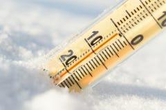 El termómetro en nieve muestra bajas temperaturas en celsius fotografía de archivo