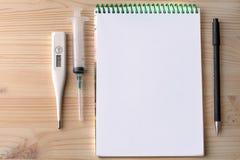El termómetro y la pluma de la jeringuilla que mienten en la tabla foto de archivo libre de regalías
