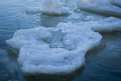 El terrón del hielo derrite lentamente en las ondas cerca de la orilla Imagenes de archivo