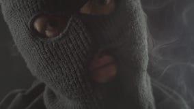 El terrorista peligroso en un pasamontañas fuma un cigarrillo y hace mucho humo almacen de metraje de vídeo