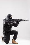 El terrorista que sostiene una ametralladora en sus manos apunta aislado sobre blanco fotos de archivo