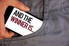 El texto de la escritura de la palabra y el ganador es El concepto del negocio para anunciar como primero coloca en empujar manua foto de archivo